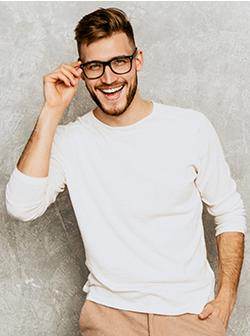 man smiling holding eyeglasses
